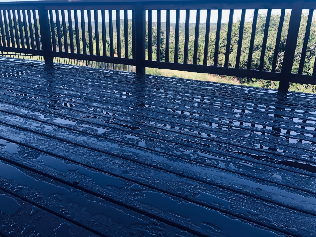A dark stained deck covered with tiny puddles of rain water.  In the background are seen green rolling hills.