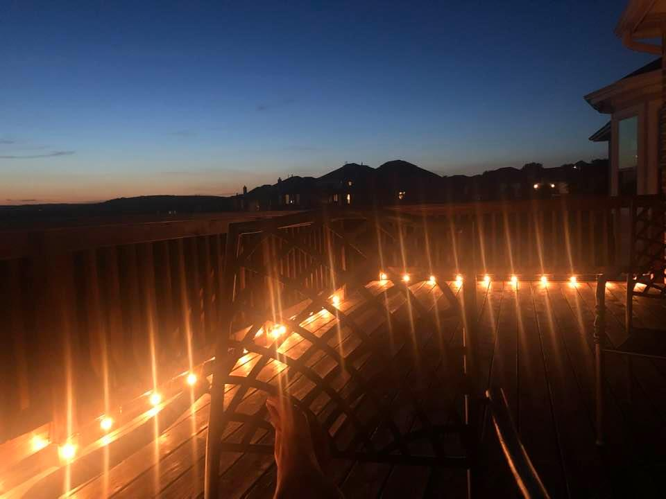 It is dusk. The evening sky is indecisive between day and night. There are fairy lights on a deck and someone is sitting on a chair with feet stretched on the opposite chair.