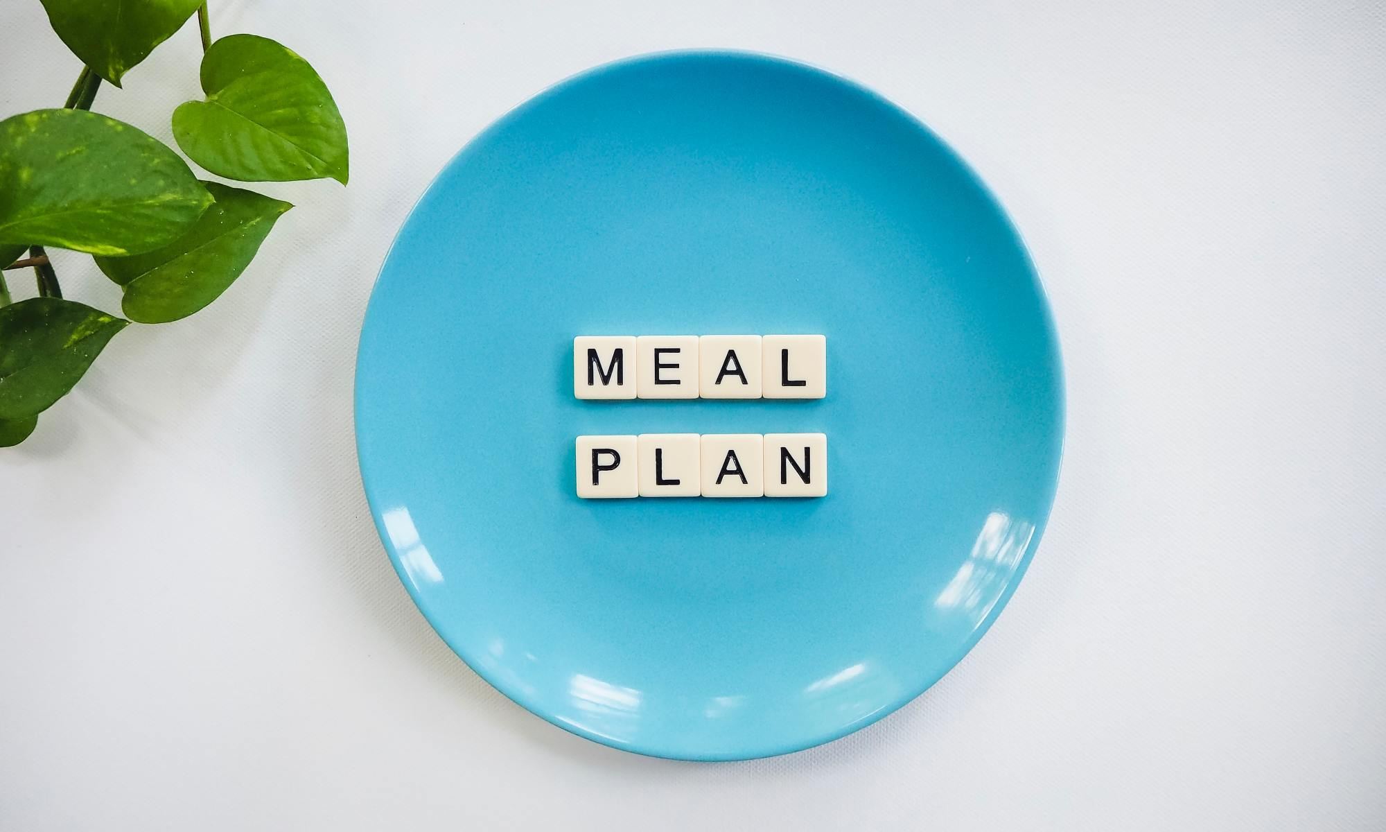 A blue plate with the words Meal Plan spelled out with scrabble tiles on it.