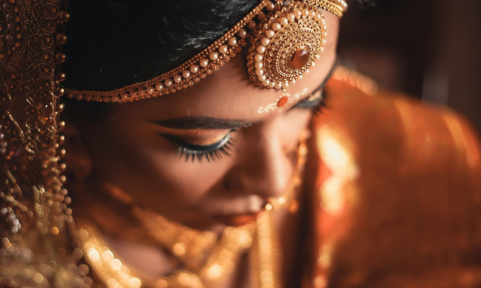 An Indian girl dressed in bridal finery, looking down, eyes, shielded, but standing tall